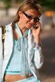 Jonge vrouw die op de straat loopt en op de telefoon spreekt Royalty-vrije Stock Foto