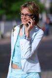 Jonge vrouw die op de straat loopt en op de telefoon spreekt Royalty-vrije Stock Afbeeldingen