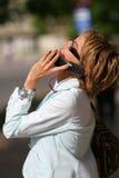 Jonge vrouw die op de straat loopt en op de telefoon spreekt Stock Foto's