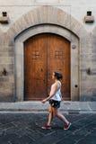 Jonge vrouw die op de straat tegen oude boogdeur lopen royalty-vrije stock foto