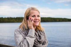 Jonge vrouw die op de telefoon en het glimlachen spreken Stock Afbeeldingen