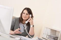 Jonge vrouw die op de telefoon op kantoor spreekt Royalty-vrije Stock Afbeeldingen
