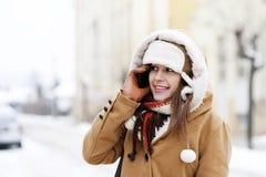 Jonge vrouw die op de telefoon spreekt Stock Afbeeldingen