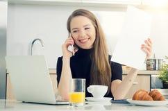 Jonge vrouw die op de telefoon spreken, die in huis werken Royalty-vrije Stock Afbeelding