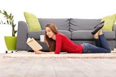 Jonge vrouw die op de vloer liggen en een boek lezen Royalty-vrije Stock Foto
