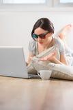 Jonge vrouw die op de vloer voor laptop ligt Royalty-vrije Stock Fotografie