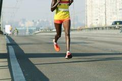 Jonge vrouw die op de weg van de stadsbrug lopen Marathon die in het ochtendlicht lopen Het lopen op stadsweg De voeten van de at royalty-vrije stock afbeelding