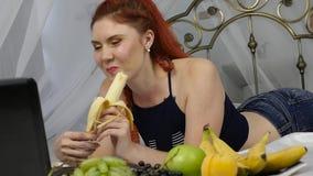 Jonge vrouw die op een bed genieten van, laptop met behulp van en een banaan thuis in de ochtend eten Langzame Motie stock footage