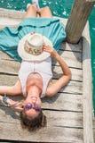 Jonge vrouw die op een dok liggen royalty-vrije stock afbeeldingen