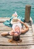 Jonge vrouw die op een dok liggen royalty-vrije stock foto