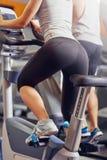 Jonge vrouw die op een geschiktheid van de fietsgymnastiek berijden stock foto