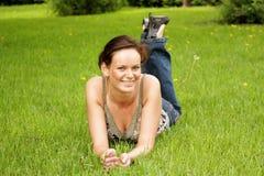 jonge vrouw die op een groen gazon liggen stock foto's