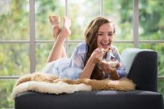 Jonge vrouw die op een laag liggen die een kom yoghurt houden stock foto