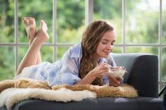 Jonge vrouw die op een laag liggen die een kom yoghurt houden royalty-vrije stock foto's