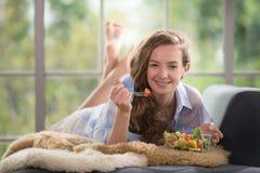 Jonge vrouw die op een laag liggen die een saladekom houden royalty-vrije stock afbeelding