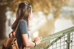 Jonge vrouw die op een leuning in de herfst leunen royalty-vrije stock fotografie