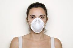 Jonge vrouw die op een masker tegen varkensgriep zet Royalty-vrije Stock Foto's