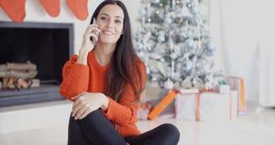 Jonge vrouw die op een mobiele telefoon spreekt Stock Afbeeldingen