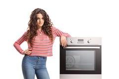 Jonge vrouw die op een oven leunen stock fotografie