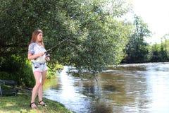 Jonge Vrouw die op een rivier in Duitsland vissen Stock Fotografie