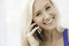 Jonge vrouw die op een smartphone spreken Stock Afbeeldingen