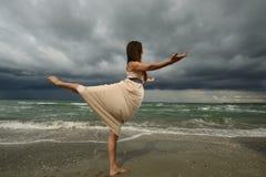 Jonge vrouw die op een strand danst Stock Afbeeldingen