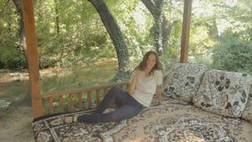 Jonge vrouw die op een tapijt in gazebo in het hout liggen stock footage
