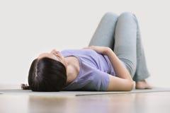 Jonge vrouw die op een yogamat liggen stock fotografie