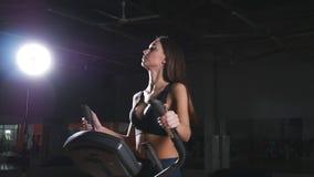 Jonge vrouw die op elliptische machine uitoefenen stock footage