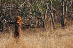 Jonge vrouw die op gouden droog grasgebied lopen royalty-vrije stock afbeelding