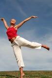 Jonge vrouw die op gras danst Stock Foto