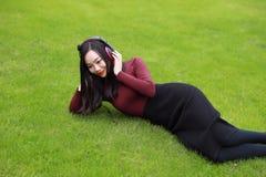 Jonge vrouw die op gras liggen en aan muziek met hoofdtelefoons luisteren stock foto