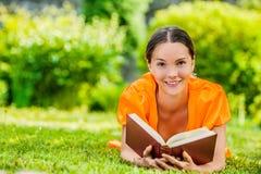 Jonge vrouw die op gras met boek liggen Stock Afbeelding