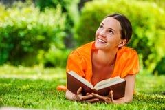 Jonge vrouw die op gras met boek liggen Royalty-vrije Stock Foto