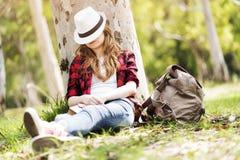 Jonge vrouw die op groen gras met de hoed over haar gezicht dutten stock foto's