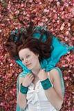 Jonge vrouw die op grond legt die met bloemblaadjes wordt behandeld Royalty-vrije Stock Foto's