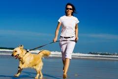 Jonge vrouw die op het strand loopt stock afbeeldingen