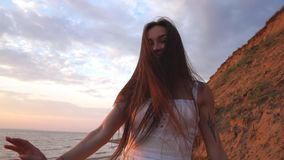 Jonge vrouw die op het strand lopen die in camera stellen stock footage