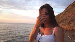 Jonge vrouw die op het strand lopen die in camera stellen stock videobeelden
