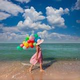 Jonge vrouw die op het strand met gekleurde ballons/Reis lopen Stock Foto's
