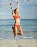 Jonge vrouw die op het strand springt Royalty-vrije Stock Afbeeldingen