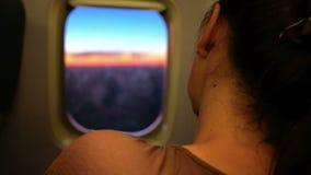 Jonge vrouw die op het vliegtuig tijdens de vlucht rusten Zij slaapt en let op de mooie zonsopgang door de patrijspoort stock video
