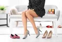 Jonge vrouw die op high-heeled schoenen proberen royalty-vrije stock afbeelding