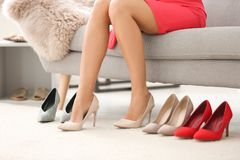 Jonge vrouw die op high-heeled schoenen proberen stock afbeelding