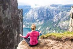 Jonge vrouw die op kjerag wandelen Het gelukkige meisje geniet van mooi meer en goed weer in Noorwegen Stock Foto's