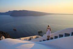 Jonge vrouw die op kleurrijke mooie zonsondergangmening van Middellandse Zee, eilanden, boa en overzees op wit openluchtterras le stock foto's