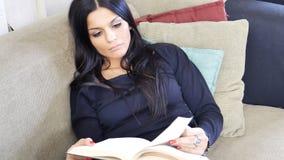 Jonge vrouw die op laag liggen en een boek lezen stock fotografie
