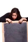 Jonge vrouw die op leeg bord richt. Stock Foto's