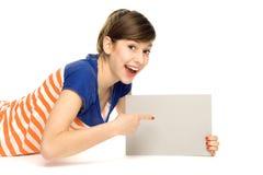 Jonge vrouw die op lege affiche richt Stock Foto's