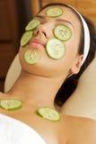 Jonge vrouw die op massagelijst liggen met komkommers op ogen en gezicht royalty-vrije stock fotografie